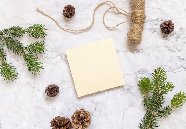 Zimowa kompozycja świąteczna z kwadratową kartą płasko leżał. boże narodzenie i nowy rok szablon karty z pozdrowieniami z gałęzi jodły, szyszki i liny na marmurowym tle widok z góry. makieta wakacje.