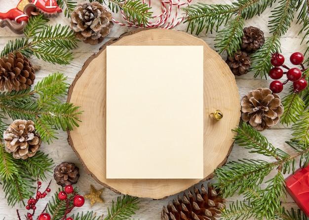 Zimowa kompozycja świąteczna z pustą kartą na drewnianym stole płasko leżał. boże narodzenie i nowy rok szablon karty z pozdrowieniami z gałęzi jodły, szyszki i ozdoby widok z góry. makieta wakacje.