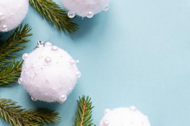 Zimowa kompozycja z gałęzi jodłowych i białych bombek. pastelowy niebieski z miejsca na kopię.