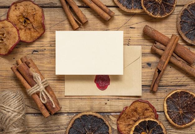 Zimowa kompozycja z pustą kartą i zapieczętowaną kopertą z przyprawami i suszonymi owocami