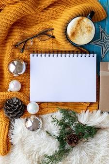Zimowa lub jesienna przytulna, płaska kompozycja. ciepły sweter z dzianiny, świąteczne zabawki, kawa, kubek i czysty papier. makieta z kartką z życzeniami i prezentem
