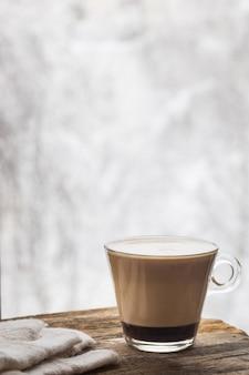 Zimowa martwa filiżanka gorącej kawy i ciepłe rękawiczki