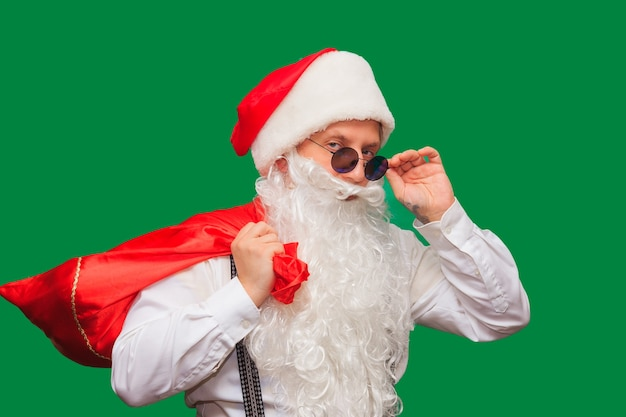 Zimowa moda i wyprzedaże. portret przystojny mężczyzna w kapeluszu santa, mrugając stojąc przed czerwoną ścianą. hipster trzyma okulary i patrzy w kamerę. miejsce na tekst.