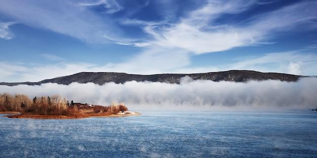 Zimowa mroźna mgła na niezamarzniętej rzece. drzewa i trawa na brzegach. krajobrazowa przyroda.