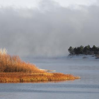 Zimowa mroźna mgła na niezamarzniętej rzece