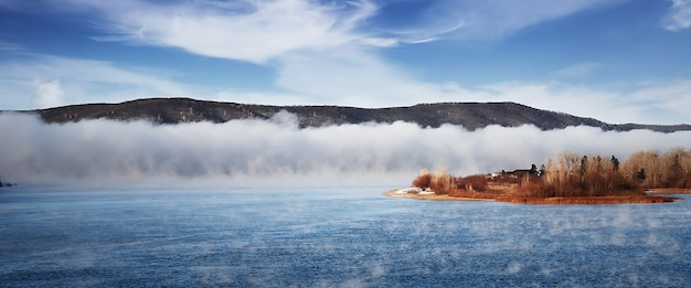 Zimowa mroźna mgła na niezamarzniętej rzece.