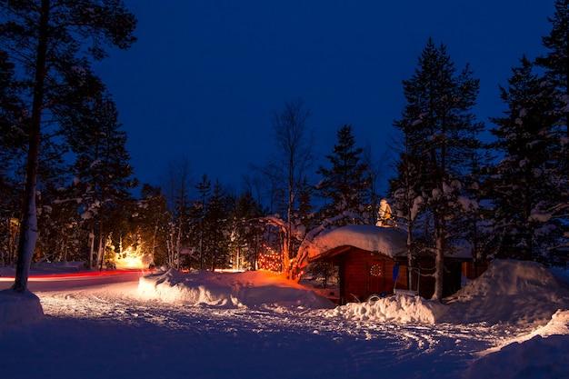 Zimowa noc. samochód kempingowy w lesie. dużo śniegu. świąteczne girlandy i ślady reflektorów