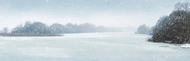 Zimowa panorama z zaśnieżoną rzeką i drzewami nad rzeką brzegową podczas opadów śniegu, światła bożego narodzenia i nowego roku w tle