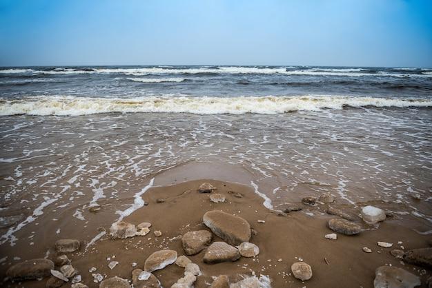 Zimowa plaża nad morzem bałtyckim jest zaśnieżona, a na morzu w saulkrasti na łotwie są duże fale