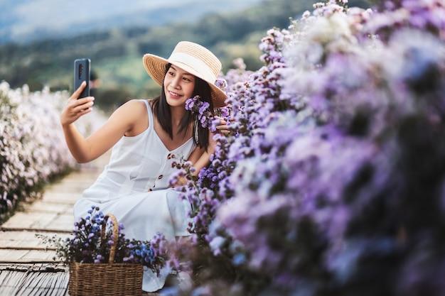 Zimowa podróż relaksująca koncepcja wakacji, młoda szczęśliwa podróżniczka azjatycka kobieta ze zwiedzaniem telefonu komórkowego na polu kwiatów margaret aster w ogrodzie w chiang mai, tajlandia