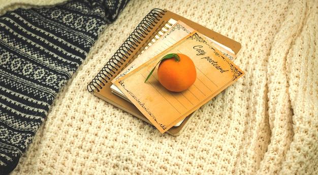 Zimowa przytulna kompozycja, książki z mandarynkami na tle dzianinowych ciepłych swetrów, baner lub makieta zdjęcia przestrzeni kopii