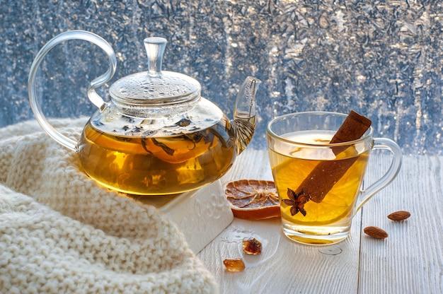 Zimowa rozgrzewająca herbata z cytryną i pomarańczą na tle mroźnych wzorów.