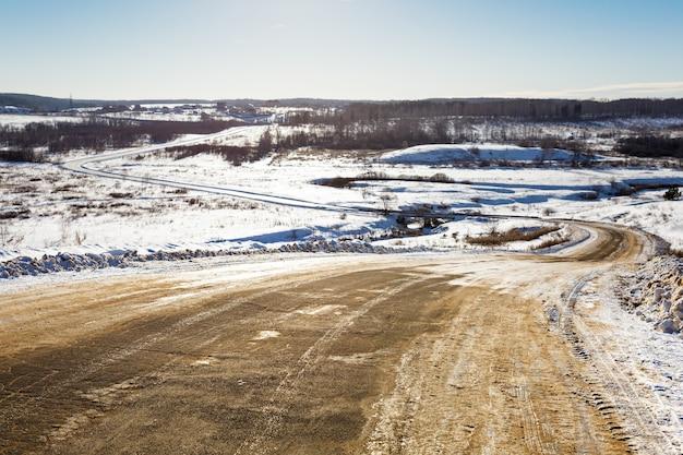 Zimowa śliska droga z zakrętami przechodząca w horyzont na jasnym słonecznym tle nieba