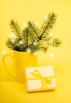 Zimowa świąteczna kompozycja w żółtym kolorze - gałązki jodły w kubku, lampki choinkowe, pudełko upominkowe diy. ozdoby świąteczne. orientacja pionowa. selektywne skupienie.