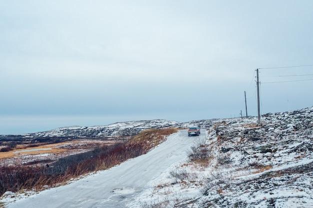 Zimowa teriberka. śliska arktyczna droga przez wzgórza.