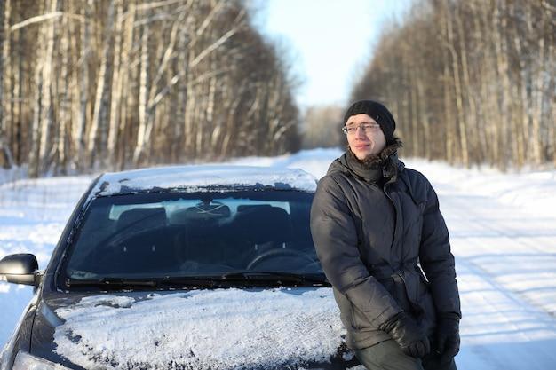 Zimowa wiejska droga w lesie w słoneczny dzień i człowiek z samochodem