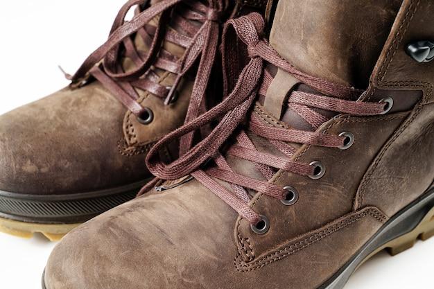 Zimowe brązowe skórzane buty męskie z żłobkowaną podeszwą na białym tle. kupuj piękne, nowoczesne buty do podróży i turystyki.