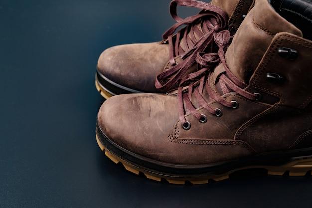 Zimowe brązowe skórzane buty męskie z żłobkowaną podeszwą na czarnym tle. kupuj piękne, nowoczesne buty do podróży i turystyki.