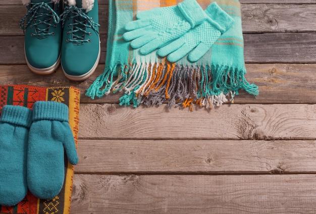 Zimowe buty, rękawiczki, szaliki na starym drewnianym stole