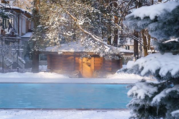 Zimowe centrum wellness spa z odkrytym basenem ze strumieniem wody termalnej w zamarzniętym powietrzu