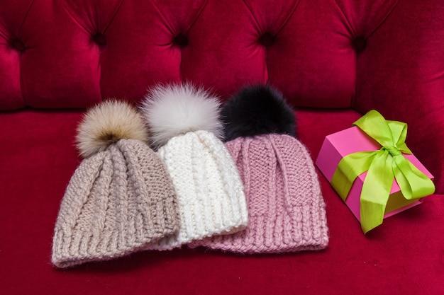 Zimowe czapki z dzianiny z futrzaną kulką leżały na czerwonej kanapie. dzianinowe czapki i prezent sylwestrowy