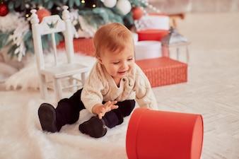 Zimowe dekoracje świąteczne. Ciepłe kolory. Piękna mała dziewczynka bawić się z teraźniejszymi pudełkami