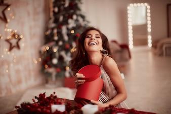 Zimowe dekoracje świąteczne. Ciepłe kolory. Urocze kobiety brunetka w beżowej sukience