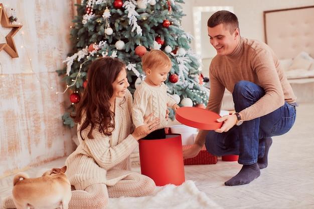 Zimowe dekoracje świąteczne. ciepłe kolory. mama, tata i mała córka bawią się z psem