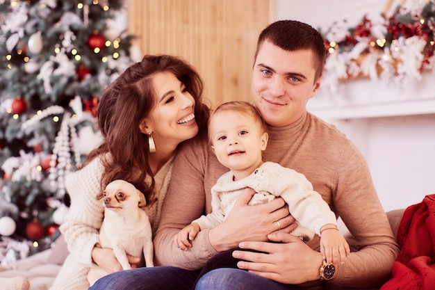 Zimowe dekoracje świąteczne. ciepłe kolory. portret rodzinny. mamo, tato i ich mała córeczka
