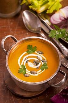 Zimowe gotowanie, zdrowa żywność. zupa dyniowa na rustykalne drewniane tła