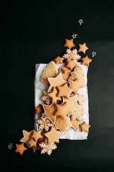 Zimowe imbirowe ciasteczka w kształcie gwiazdy na drewnianej desce świąteczny zestaw ciasteczek