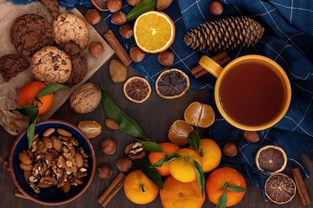 Zimowe jedzenie komfortowe - czekoladowe ciasteczka, orzechy, mandarynki i herbata