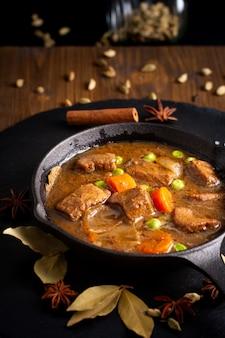 Zimowe jedzenie koncepcja domowej roboty gulasz z mięsa ekologicznego lub bourguignon w żeliwnych rynienkach