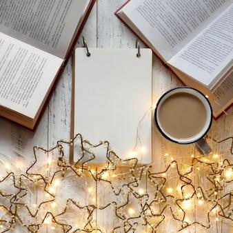 Zimowe książki. zimowe czytanie. zrobić listę na ferie zimowe. lista zakupów filiżanka herbaty i świecąca girlanda. zima. plany na boże narodzenie. pusty notatnik i świecąca girlanda