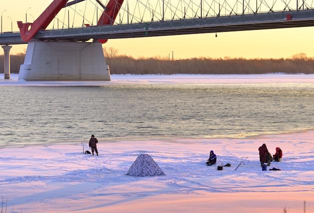 Zimowe łowienie pod lodem grupa rybaków na lodzie rzeki ob pod łukiem