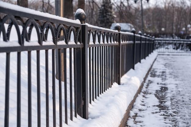 Zimowe metalowe ozdobne ogrodzenie na śniegu