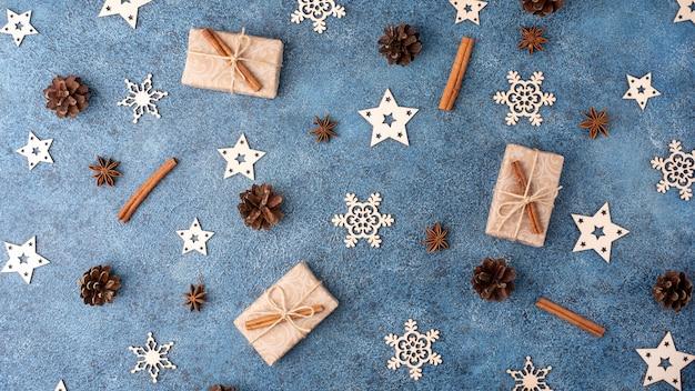 Zimowe mieszkanie leżało z cynamonem, anyżem, szyszkami, drewnianymi płatkami śniegu i prezentami w papierze rzemieślniczym na niebieskim tle tekstury. koncepcja na boże narodzenie i nowy rok.