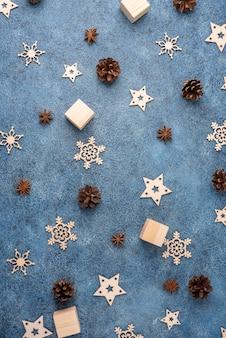 Zimowe mieszkanie leżało z cynamonem, anyżem, szyszkami, drewnianymi płatkami śniegu na niebieskim tle tekstury. koncepcja na boże narodzenie i nowy rok.