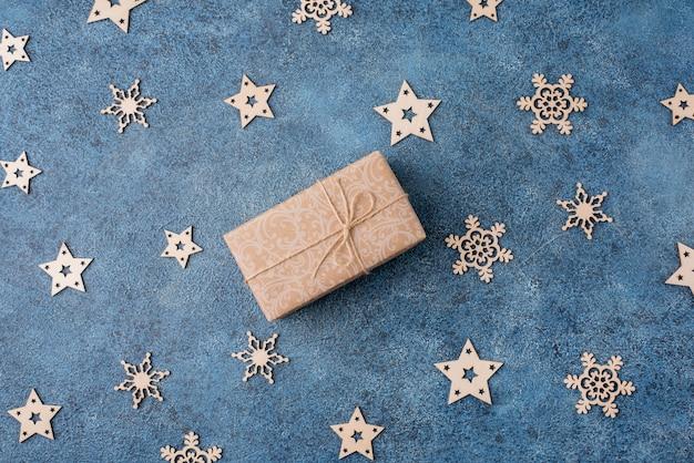Zimowe mieszkanie leżało z drewnianymi płatkami śniegu i prezentami w papierze rzemieślniczym na niebieskim tle. koncepcja na boże narodzenie i nowy rok.