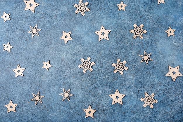 Zimowe mieszkanie leżało z drewnianymi płatkami śniegu na niebieskim tle. koncepcja na boże narodzenie i nowy rok.