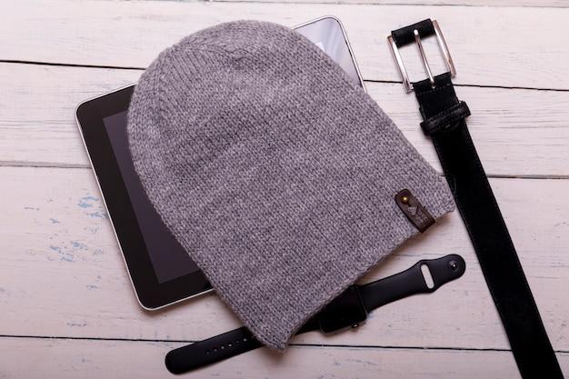 Zimowe mieszkanie leżało ze smartwatchem, tabletem, czapką i paskiem na białym rustykalnym drewnianym stole. boże narodzenie i nowy rok w tle.