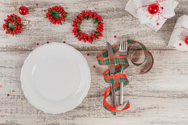 Zimowe nakrycie z dekoracjami świątecznymi i noworocznymi na białym drewnianym stole. świąteczne nakrycie stołu na świąteczny obiad. leżał na płasko