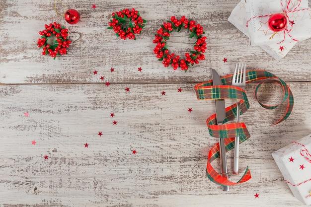 Zimowe nakrycie z dekoracjami świątecznymi i noworocznymi na białym drewnianym stole. świąteczne nakrycie stołu na świąteczny obiad. mieszkanie leżało z miejscem na kopię tekstu