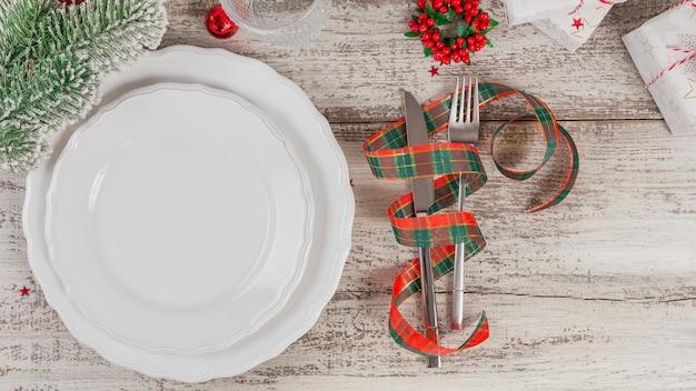 Zimowe nakrycie z dekoracjami świątecznymi i noworocznymi na białym drewnianym stole. świąteczne nakrycie stołu na świąteczny obiad. widok z góry z miejscem na kopię tekstu