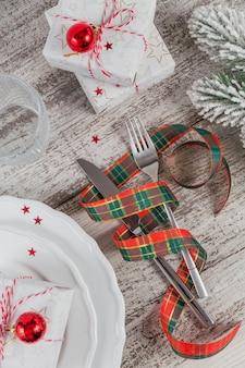 Zimowe nakrycie z dekoracjami świątecznymi i noworocznymi na białym drewnianym stole. świąteczne nakrycie stołu na świąteczny obiad. widok z góry