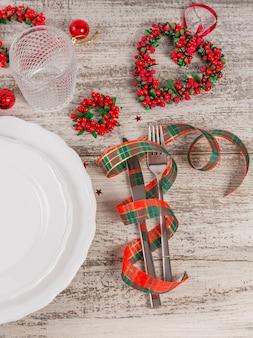 Zimowe nakrycie z dekoracjami świątecznymi i noworocznymi na białym drewnianym stole. świąteczne nakrycie stołu na świąteczny obiad.