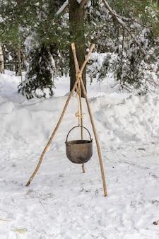 Zimowe ognisko w lesie. gotowanie w warunkach polowych