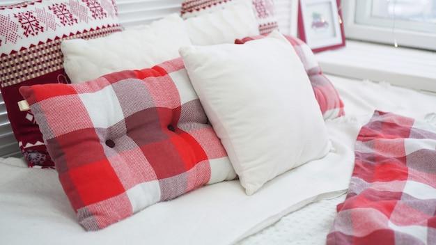 Zimowe ozdoby świąteczne. czerwone białe poduszki na łóżku.