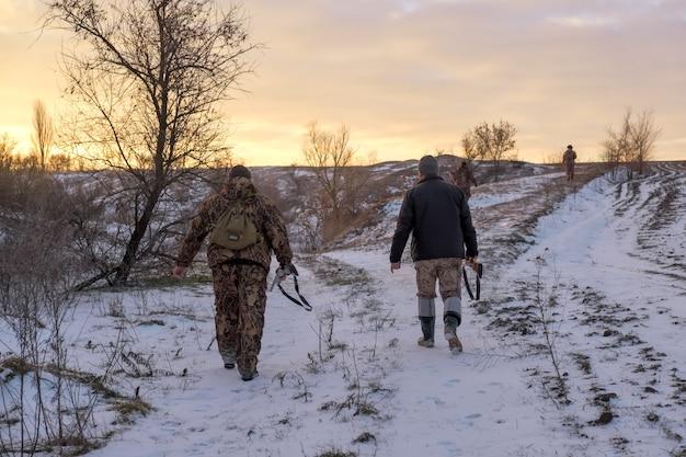 Zimowe polowanie na zające. ludzie ze strzelbami szukający modlitwy.