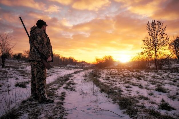 Zimowe polowanie na zające o wschodzie słońca. łowca poruszający się ze strzelbą i szukający zdobyczy.